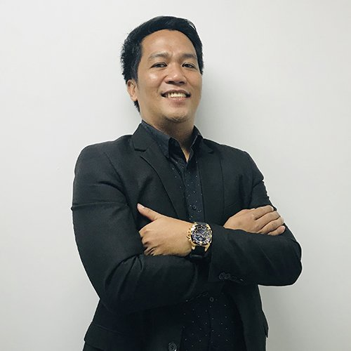 Sir teofilo smiling while crossing his arms